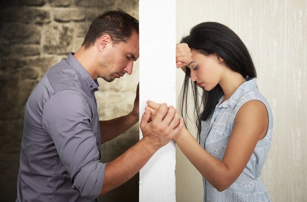 Two partners holding hands around wall showing their marriage struggles who are starting infidelity therapy with infidelity marriage counselors.
